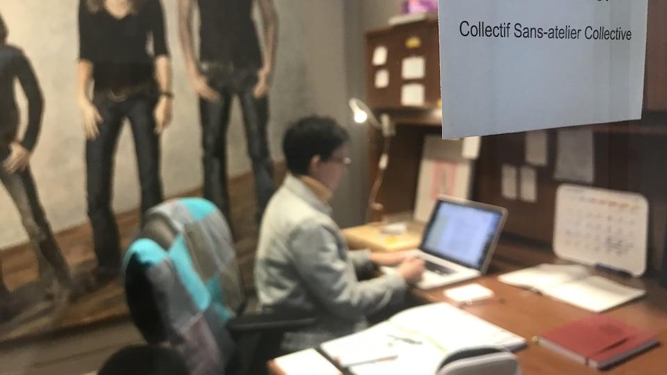 Zoé Fortier dans un bureau à travers une vitre où il est écrit sur un papier «collectif Sans-atelier Collective»