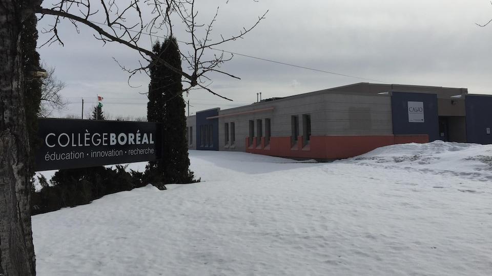 Le collège vu en hiver. Une pancarte avec le nom de l'établissement occupe le devant de la photo.