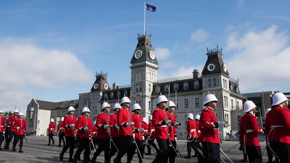 Des élèves officiers en uniforme lors d'une parade militaire devant le collège.