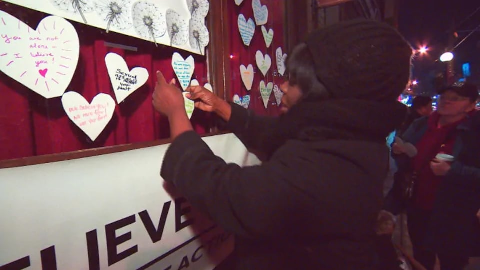 Une femme colle un message en forme de coeur sur la vitrine d'un bar.