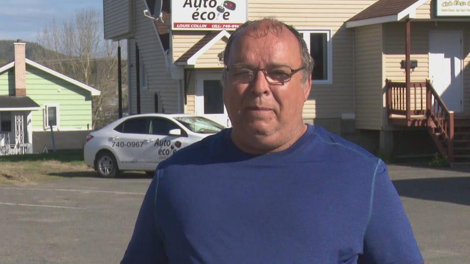 Louis Collin interviewé devant le bâtiment de son école de conduite.