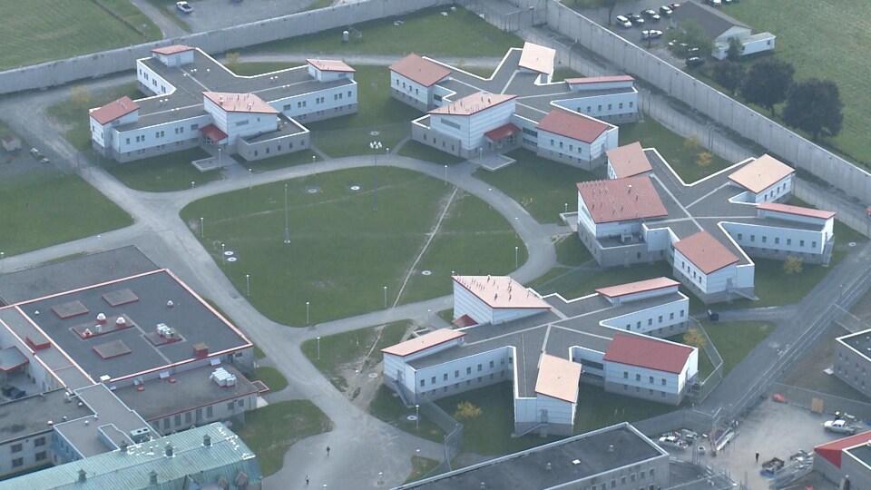 Cinq unités d'incarcération à sécurité moyenne et une grande cour de verdure au centre vus du ciel.