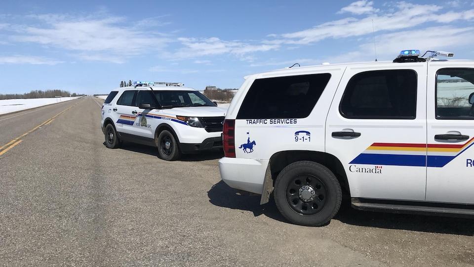 Deux véhicules de la GRC sont stationnés sur la route.