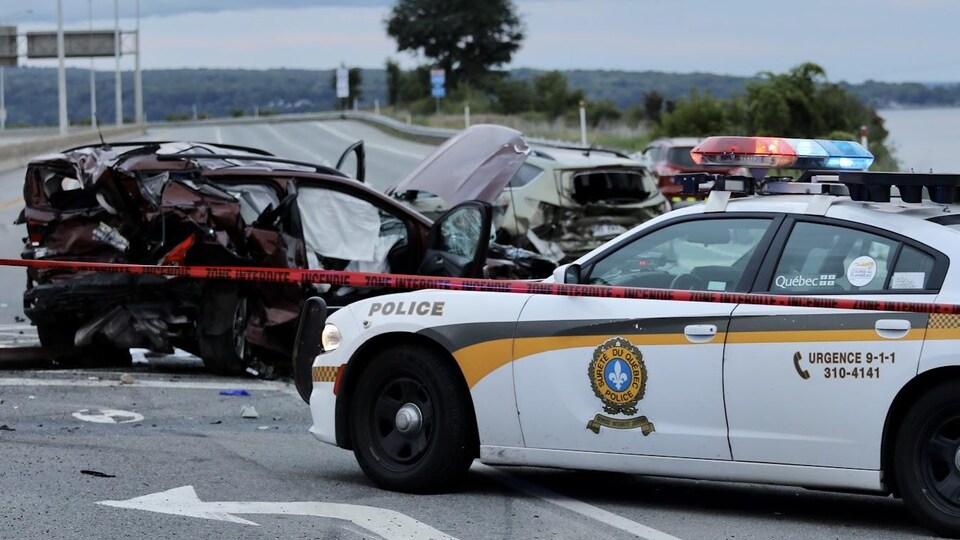 Un véhicule très accidenté et une voiture de la Sûreté du Québec.