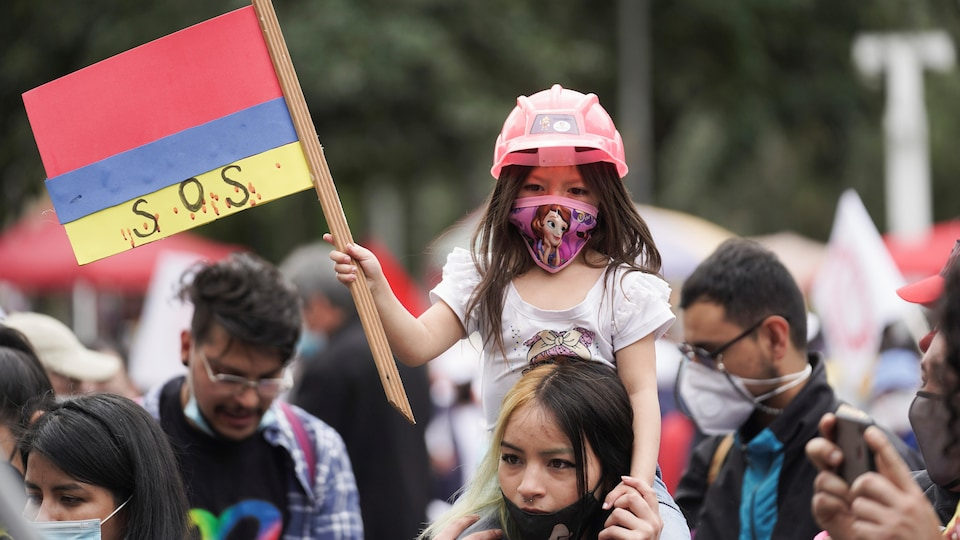 Une petite fille sur les épaules d'une adulte portant un masque et brandissant un drapeau au milieu de manifestants.