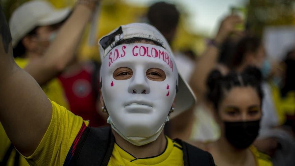 Un homme porte un masque sur lequel il est écrit SOS Colombia.