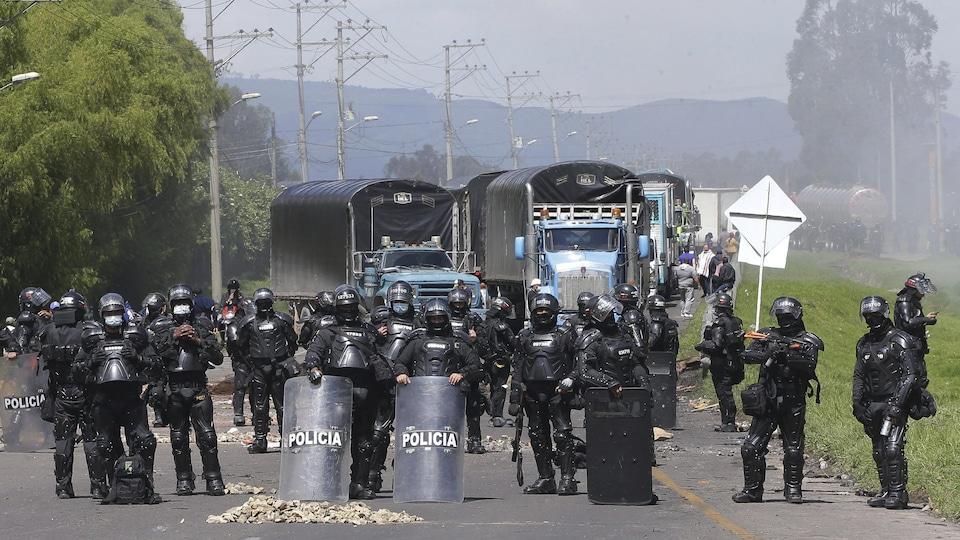 Des policiers face à un barrage de camions.
