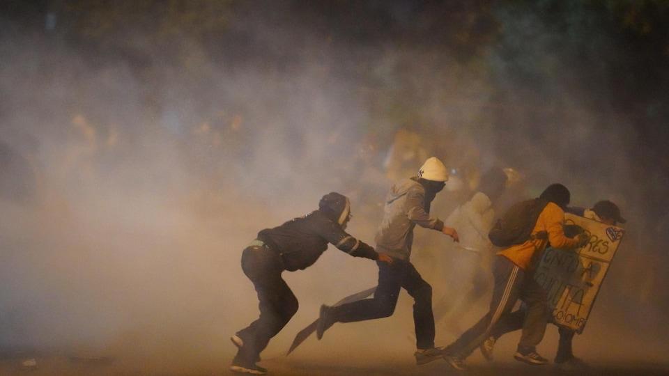 Des manifestants tentent de courir alors que du gaz lacrymogène s'échappe à Bogota.