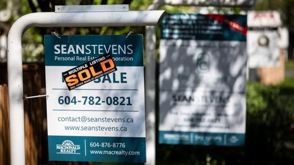 Une pancarte où il est écrit « vendu » devant une maison.