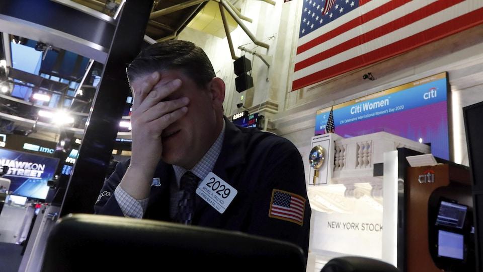 Un homme avec la main sur le visage à la Bourse de New York.