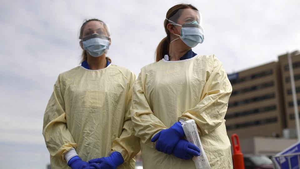 Deux infirmières portent des masques respiratoires et une jaquette protectrice à l'extérieur d'un hôpital.
