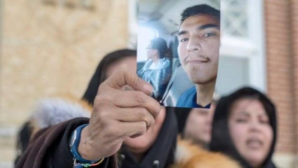 La mère de Colten Boushie, mort par balle en 2018, montre une photo de son fils.