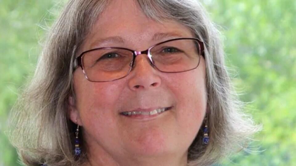Portrait de Sarah Colwell, souriante, devant un arbre en été