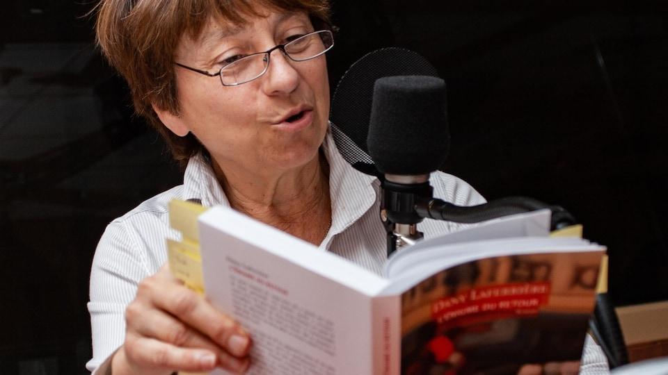 En studio, la panéliste Françoise David lisant un extrait du livre qu'elle défend.