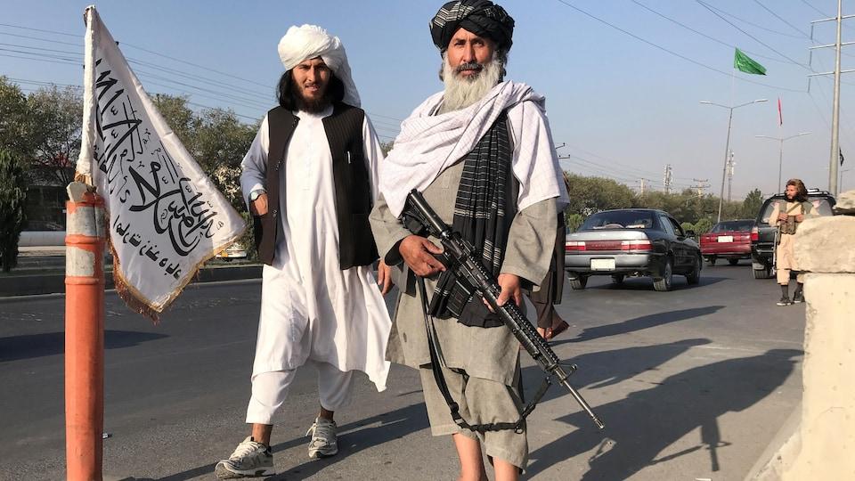 Des talibans armés arborent un air victorieux.