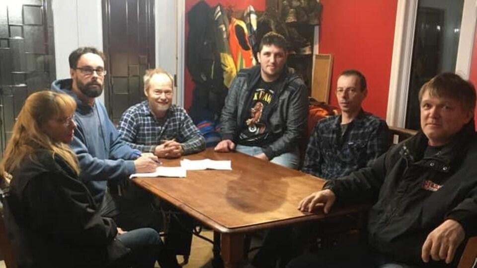 Une femme et cinq homme sont assis autour d'une table de cuisine.