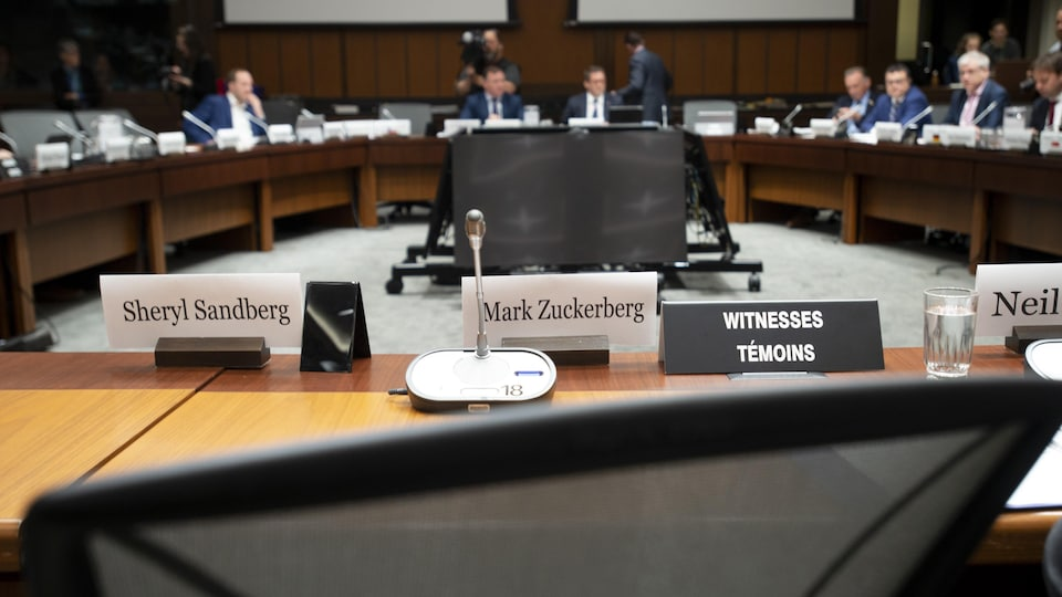 Les noms de Sheryl Sandberg et de Mark Zuckerberg sont affichés, devant des chaises vides.