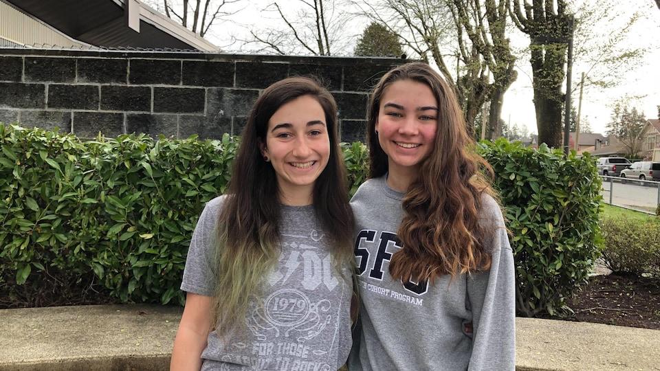 Deux jeunes femmes aux cheveux longs et souriantes posent pour la photo.
