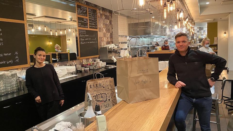 Une femme et un homme, séparé par un comptoir, dans un restaurant.