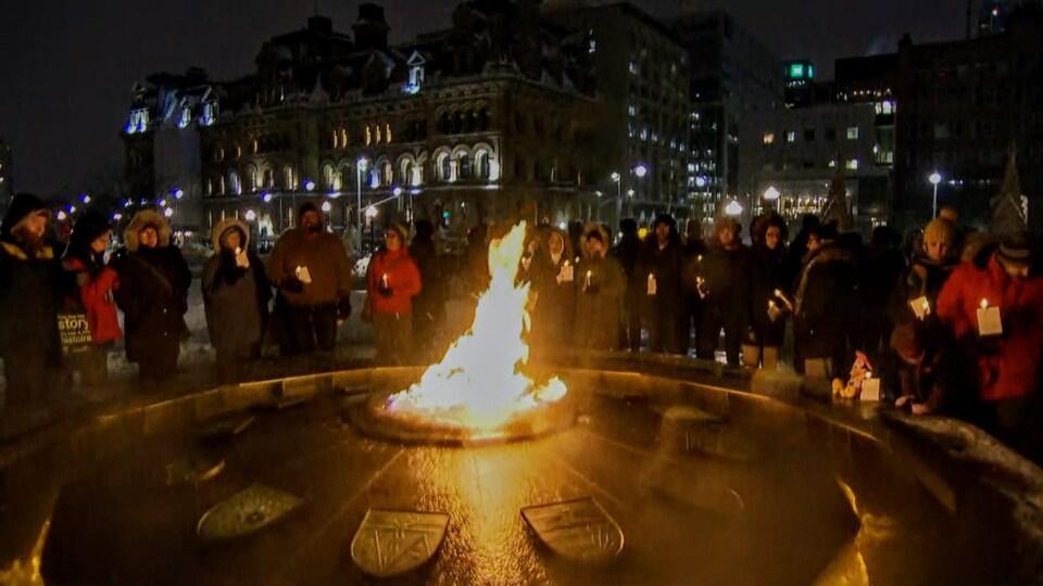 Des dizaines de personnes rassemblées autour d'une flamme