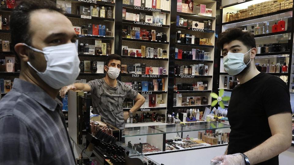 Des hommes portant masques et gants discutent dans une parfumerie.