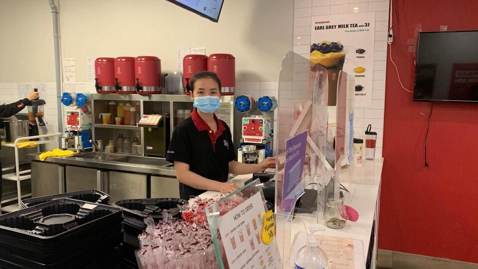 Une jeune femme travaille au comptoir d'un magasin qui vend des thés à bulles.
