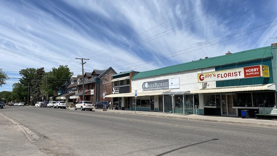 La 13e rue à Regina, par une journée d'été ensoleillée. Quelques nuages dessinent le ciel.