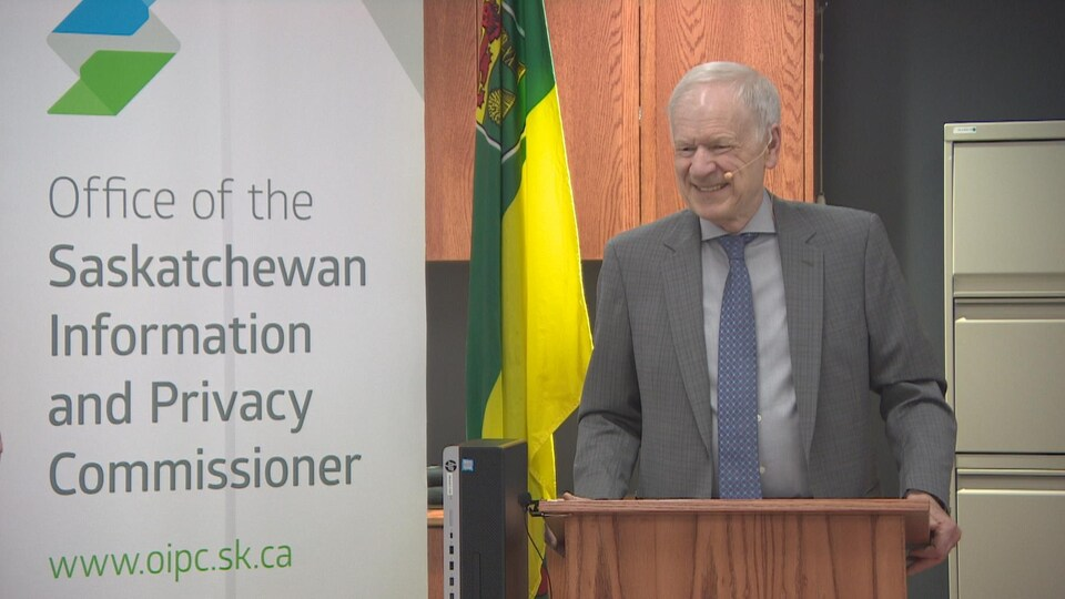Ronald Kruzeniski, souriant, se tient debout derrière un pupitre durant une rencontre avec des journalistes.