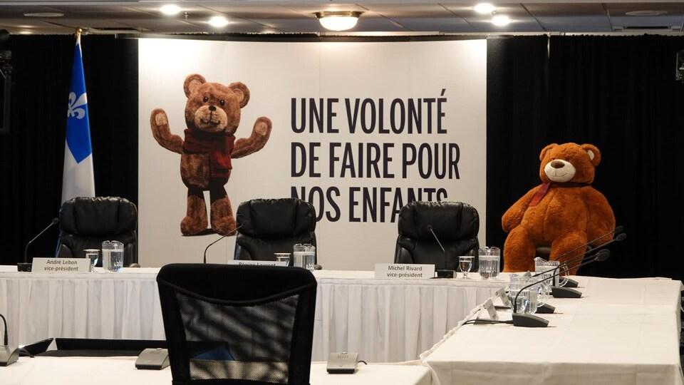 Un ourson en peluche à côté d'une affiche de la commission Laurent