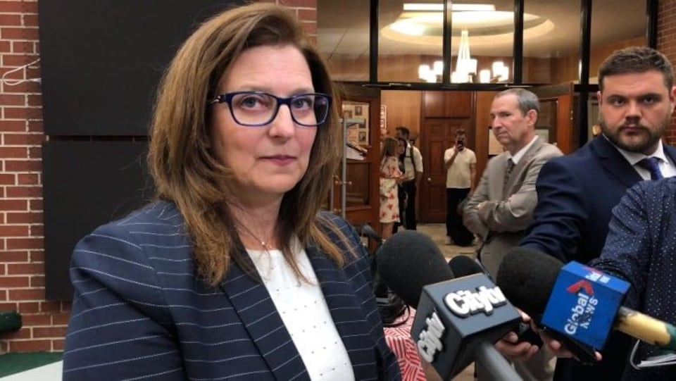 Angela Mancini est entourée des micros des journalistes lors d'un point de presse.