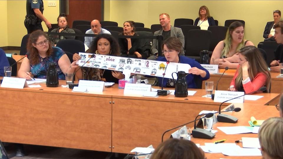 Quatre jeunes femmes assises dans une salle d'audience déroulent une banderole.