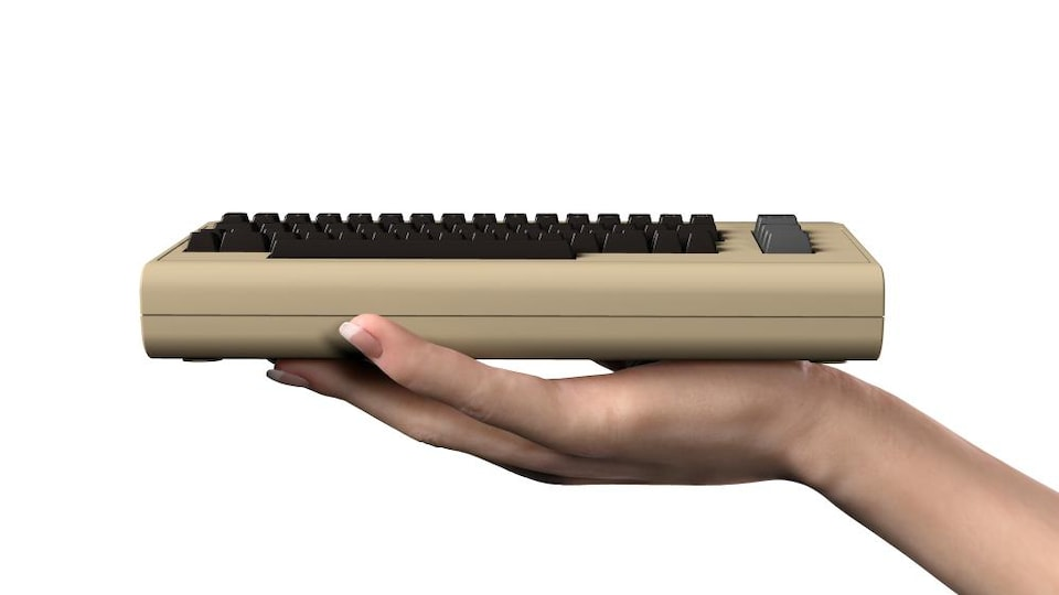 Une photo montrant le C64 Mini, qui ressemble à un gros clavier beige, dans la main d'une personne.
