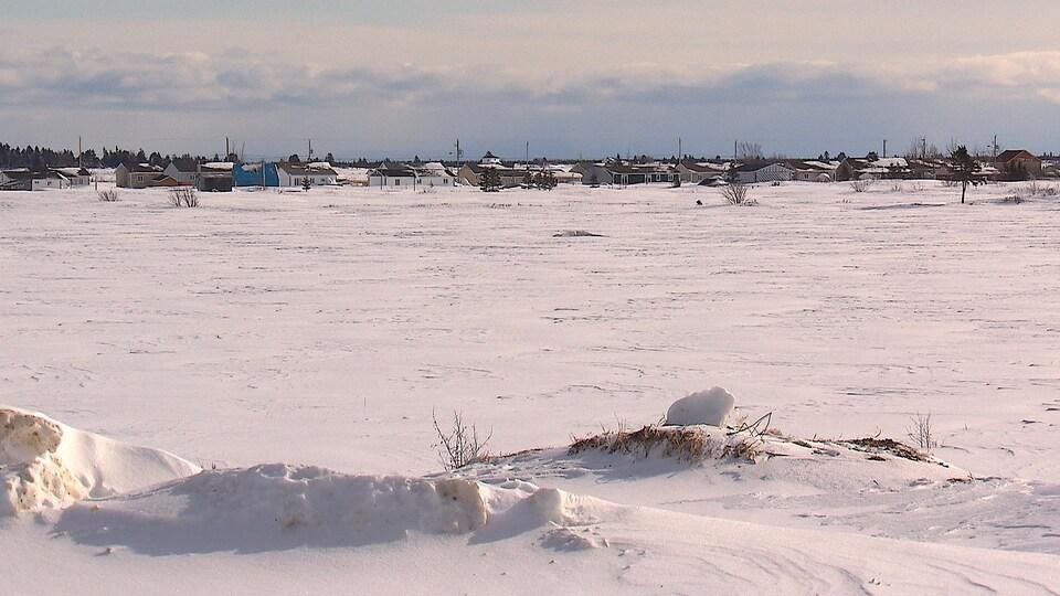 Au bout d'un champ enneigé, des maisons sont alignées.