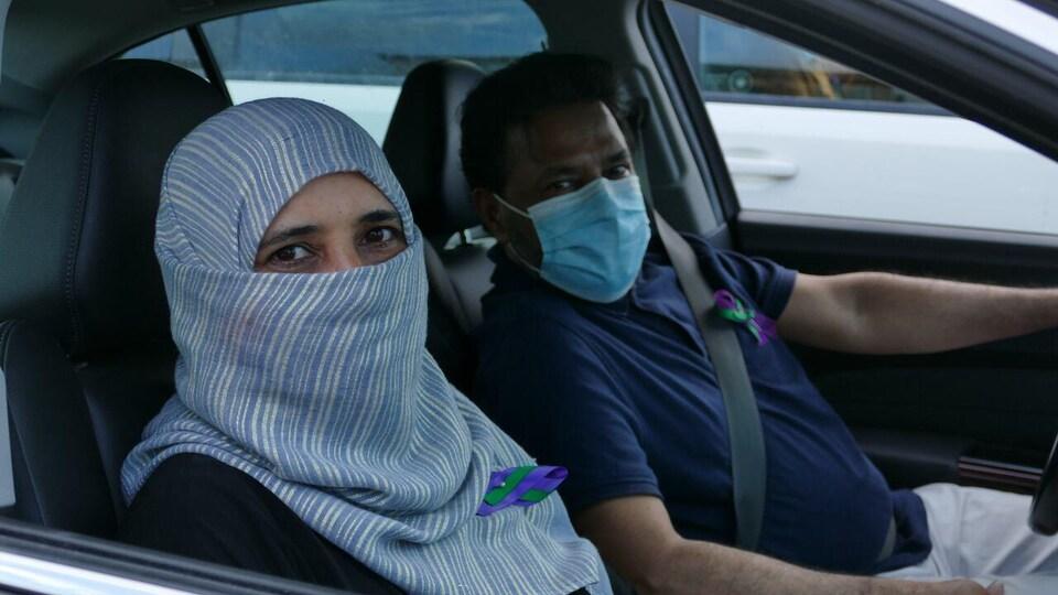 Une femme voilée et un homme sont à bord de leur véhicule.