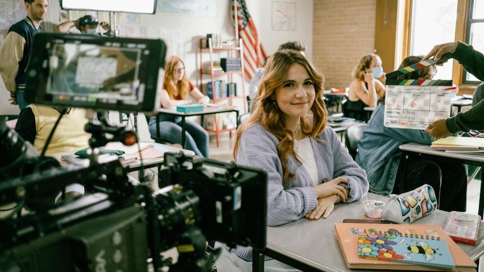 La femme est assise dans une salle de classe. Une caméra de télévision est devant elle, plusieurs personnes sont derrière elle et une clapette de cinéma est à côté d'elle.