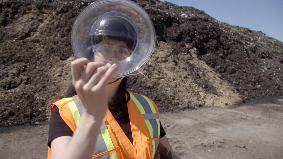 Une femme tient un plat de plastique près d'un tas de compost.