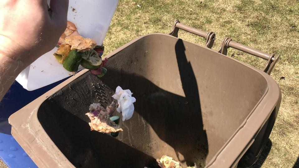 Quelqu'un verse des déchets de table dans un bac de compost brun.