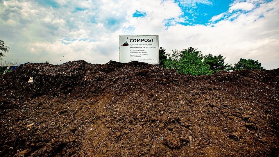"""Un grand tas de compost brun, à l'extérieur. Au sommet, une pancarte blanche indique """"compost""""."""