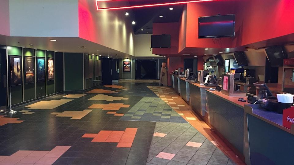 Comptoir de restauration du cinéma 9, avec plancher carrelé, entrée des salles de cinéma et néon au plafond.
