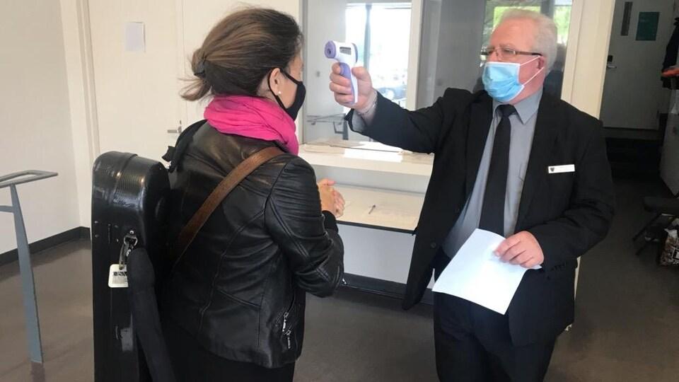 Un homme masqué prend la température d'une musicienne masquée à l'aide d'un thermomètre infrarouge.