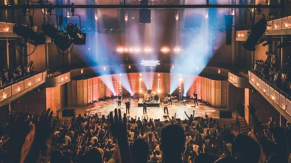 Des musiciens jouent sur une scène devant un public dans une grande salle de concert.