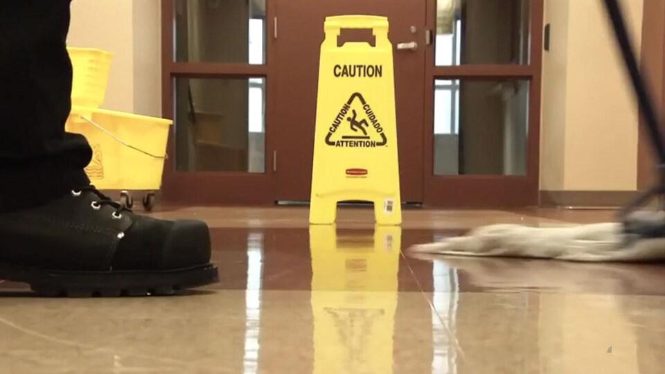 Image d'un concierge passant la vadrouille sur un plancher d'un édifice à bureau.