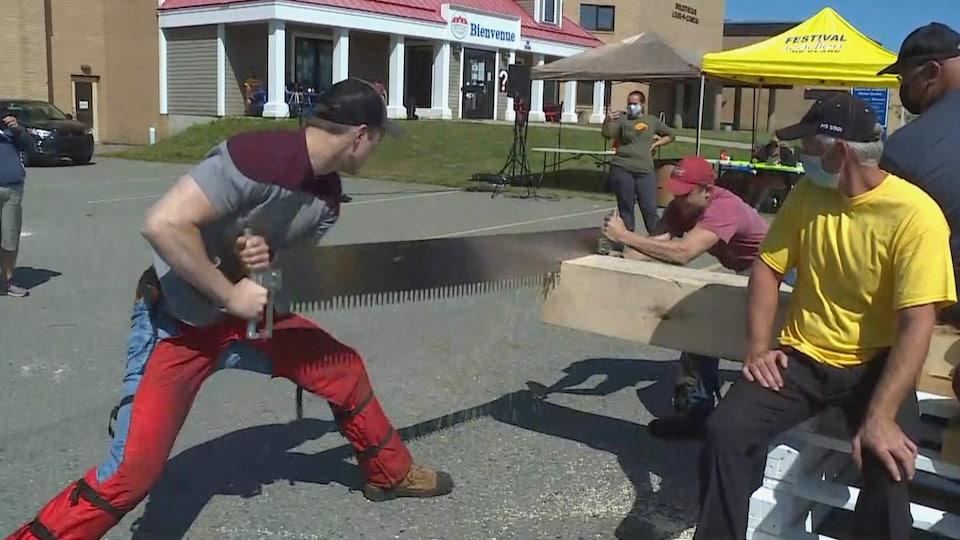Deux hommes coupent un madrier à la main avec une scie devant des témoins.