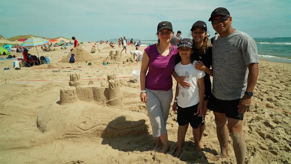 Une famille pose devant une sculpture représentant un château sur le dos d'une baleine.