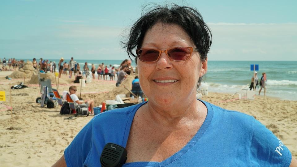Une femme portant des lunettes fumées sourit à la caméra.