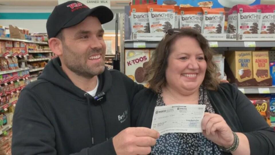 Un homme et une femme tiennent un chèque dans leurs mains.