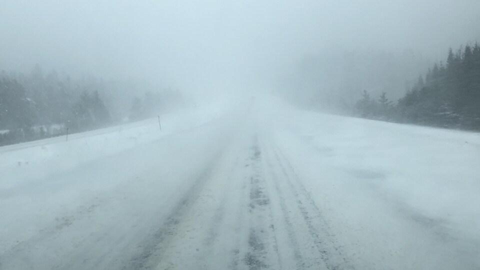De la neige et des plaques de glace recouvrent une route.