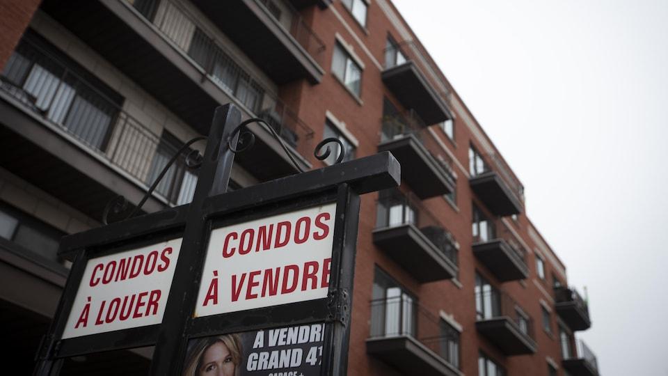 Pancarte indiquant des condos à vendre et à louer avec un édifice en arrière plan.