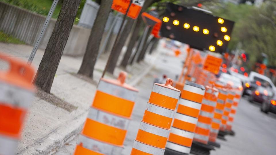 Des cônes orange et une flèche clignotante détournent la circulation près d'un chantier de construction.