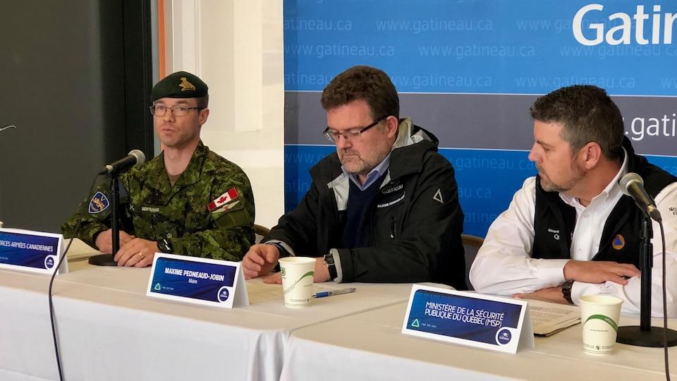 Trois intervenants assis à une table lors d'un point de presse.
